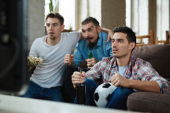 Passionés du football émotifs regardant la rencontre à la TV Image stock