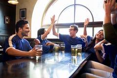 Passionés du football avec de la bière célébrant la victoire à la barre Photographie stock libre de droits