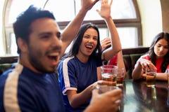 Passionés du football avec de la bière célébrant la victoire à la barre Photos stock