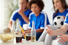 Passionés du football avec des boissons et des puces à la maison Photographie stock libre de droits