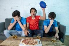 Passionés du football déçus et heureux observant un match de football Image libre de droits