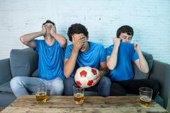 Passionés du football déçus observant un match de football Photos libres de droits