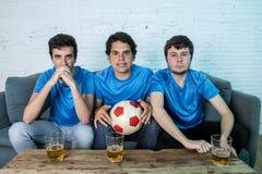 Passionés du football déçus observant un match de football Photographie stock
