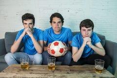 Passionés du football déçus observant un match de football Images stock