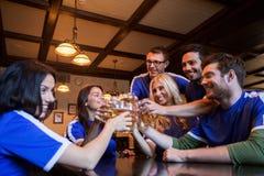 Passionés du football faisant tinter des verres de bière à la barre de sport Photographie stock libre de droits