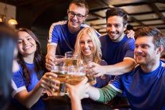 Passionés du football faisant tinter des verres de bière à la barre de sport Photographie stock