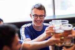 Passionés du football faisant tinter des verres de bière à la barre de sport Image stock
