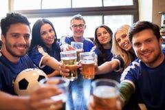 Passionés du football faisant tinter des verres de bière à la barre de sport Image libre de droits