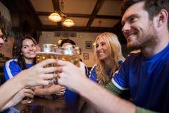 Passionés du football faisant tinter des verres de bière à la barre de sport Photos stock