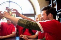 Passionés du football faisant tinter des verres de bière à la barre de sport Photo libre de droits