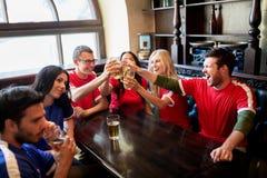 Passionés du football faisant tinter des verres de bière à la barre de sport Photos libres de droits