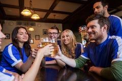 Passionés du football faisant tinter des verres de bière à la barre de sport Images stock