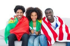 Passionés du football heureux enveloppés dans les drapeaux souriant à l'appareil-photo Photos libres de droits