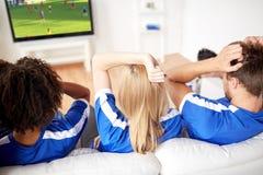 Passionés du football observant le football à la TV à la maison Image stock