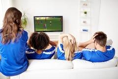 Passionés du football observant le football à la TV à la maison Photographie stock libre de droits