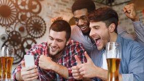 Passion?s du football observant le football sur Smartphone dans le bar photographie stock