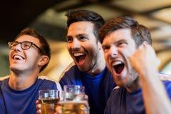 Passionés du football ou amis avec de la bière à la barre de sport Photographie stock
