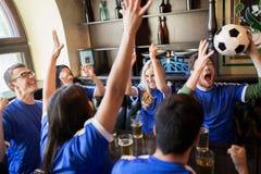 Passionés du football ou amis avec de la bière à la barre de sport Photographie stock libre de droits