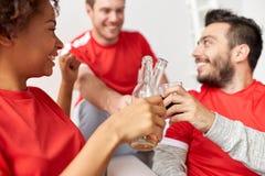 Passionés du football ou amis heureux avec de la bière à la maison Photos stock
