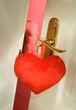 Passion. A fabric heart hangig at a door handle Stock Images