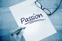 Passion  against left hand writing on white page on working desk Royalty Free Stock Photos