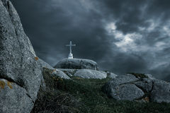 Passion of Christ. White lonely cross in a rocky hill against a dramatic sky at a sad sunset Royalty Free Stock Image