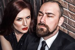 Passion concept, closeup. Bearded man closed eyes, redhead sensual woman with red lips and handsome makeup, looking at camera stock image