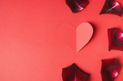 Passion concept for Valentine's day with dark rose petals and a paper heart on a red background Stock Images