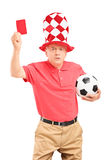 Passioné du football mûr fâché avec la boule donnant une carte rouge Photos stock