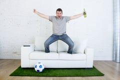 Passioné du football regardant la rencontre de TV sur le sofa avec l'herbe lancer le tapis célébrant le but Images libres de droits