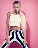 Passion emotional blond slim model with long hair posing in stri Stock Photo