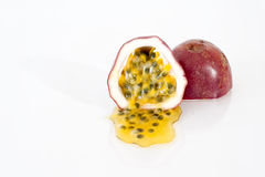 Passion fruit. Halved passion fruit on white reflective surface Royalty Free Stock Photography
