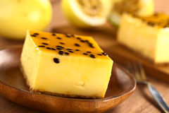 Passion Fruit Cheesecake. Fresh passion fruit cheesecake dessert on wooden plate with another piece of cake and yellow passion fruit in the back (Selective Focus Stock Photo