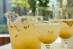 Passion fruit maracuya lemonade refreshment drink in wine glasses and pitcher. Tropical sweet seedy fruity cold beverage Stock Images