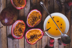 Passion fruit pulp and seed board, spoon, candied fruit, plate w. Close up yellow color passion fruit pulp and seed in small ceramic bowl  on BROWN board, spoon Stock Images