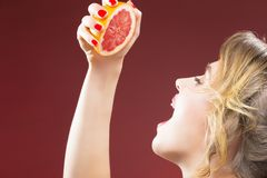 Passion Fruit Series. Closeup of Hand of Caucasian Girl Squeezing Grapefruit. Half To Her Mouth. Against Red Background. Horizontal Image royalty free stock images