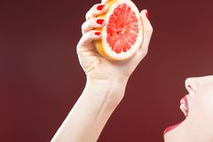 Passion Fruit Series. Closeup of Hand of Caucasian Girl Squeezing Grapefruit. Half To Her Mouth. Against Red Background. Horizontal Shot stock photo