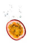 Passion fruit in water with air bubbles. Passion fruit falling into water, with air bubbles, in front of white background, union of the three things essential to royalty free stock image
