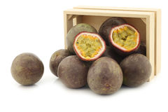 Passion fruits and a cut one in a wooden box Royalty Free Stock Image