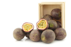 Passion fruits and a cut one in a wooden box Stock Photos