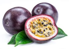 Passion fruits and its cross section with pulpy juice filled with seeds. White background.  royalty free stock photo