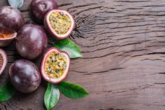Passion fruits and its cross section with pulpy juice filled with seeds. Wooden background.  royalty free stock photos