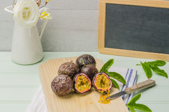 Passion fruits with leaves, knife and white flowers in jar Stock Photo