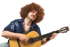 Passion for music. Hippy with old guitar totally into his music Royalty Free Stock Photos