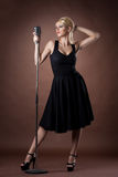 Passion singer with microphone on dark background Royalty Free Stock Images