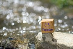 Passion on wooden block in the river. Passion on wooden block with smile face on stone in the river with shiny water real round bokeh background royalty free stock photography