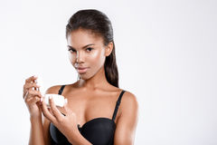 Passionate african woman holding skincare product Stock Photography