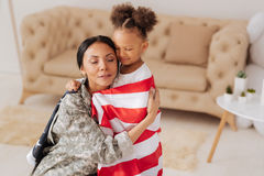 Passionate attached mom feeling very emotional. Finally here with you. Sentimental tender young women looking moved by her daughters greetings and hugging her stock photography