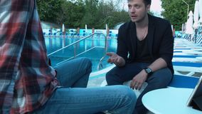 Passionate businessman explains to his partners a project near the pool. Two creative young men communicate on the hotel`s sun loungers stock video footage