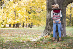 Passionate couple against tree trunk in park during autumn Royalty Free Stock Photo